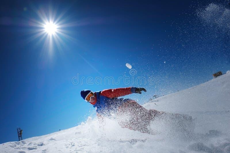 O snowboarder masculino do atleta cai na neve imagem de stock