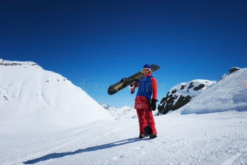 O snowboarder masculino do desportista está na perspectiva do moun foto de stock