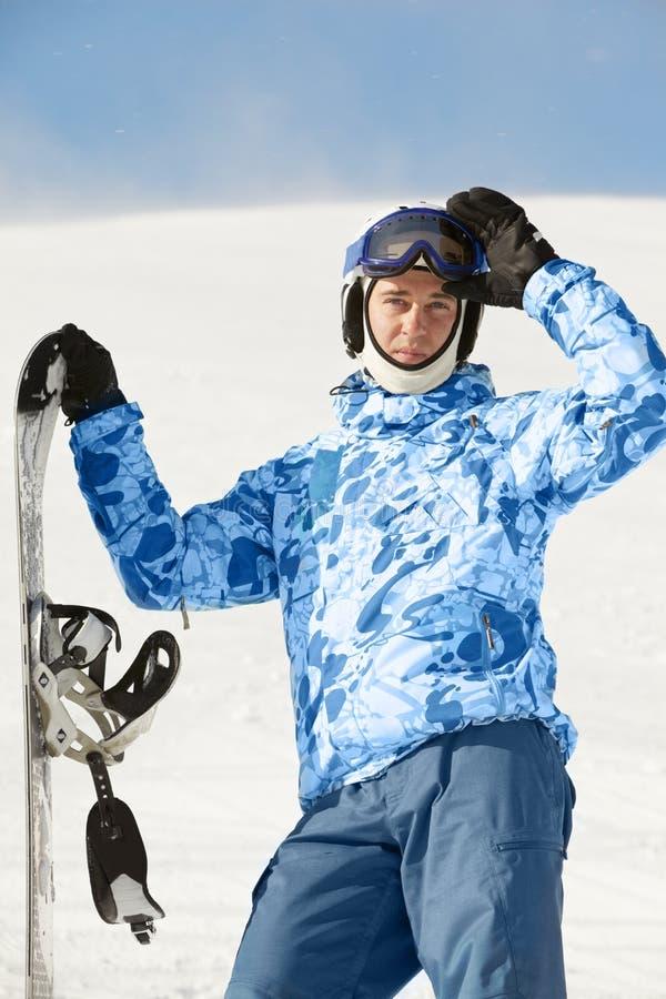 O Snowboarder no terno de esqui está com snowboard imagens de stock