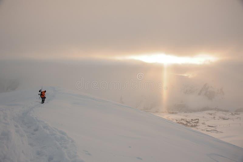 O Snowboarder que anda no pico de montanha alta sob o sol irradia imagens de stock
