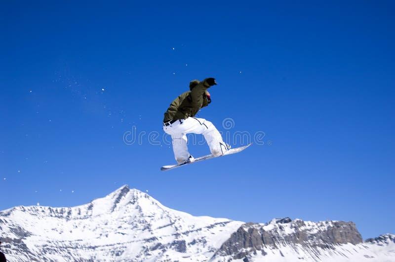 O Snowboarder que salta altamente no ar foto de stock royalty free