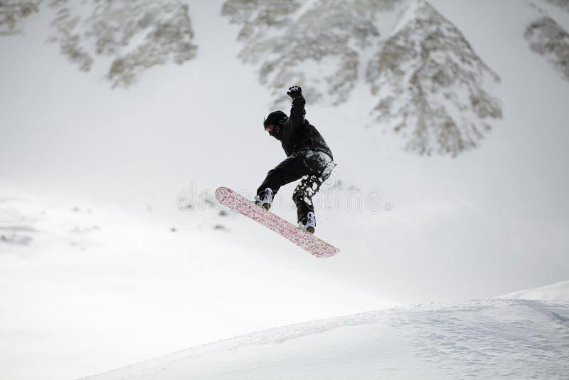 O salto do Snowboarder foto de stock