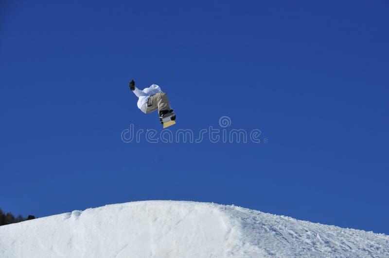 O Snowboarder que salta de uma rampa da neve imagem de stock