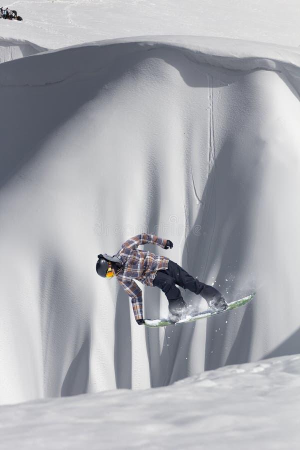 O Snowboarder salta nas montanhas, esporte do extremo do inverno foto de stock royalty free