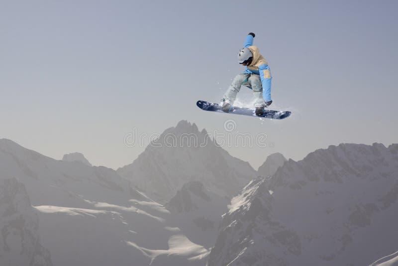 O Snowboarder salta nas montanhas, esporte do extremo do inverno fotografia de stock