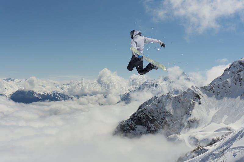 O Snowboarder salta nas montanhas, esporte do extremo do inverno fotos de stock