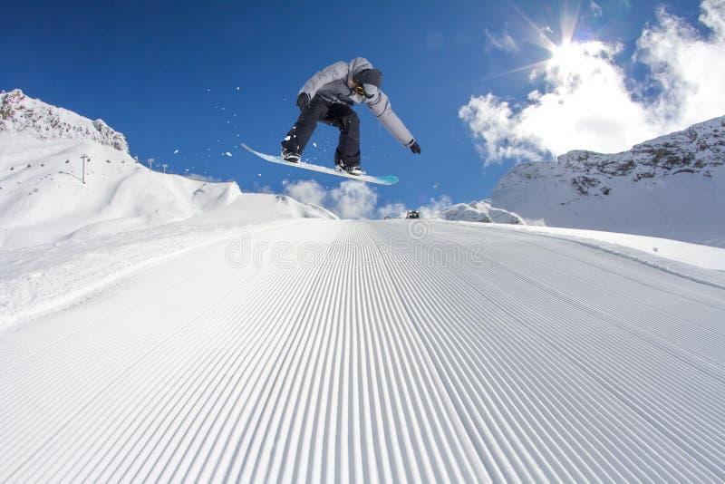 O Snowboarder salta nas montanhas, esporte do extremo do inverno foto de stock