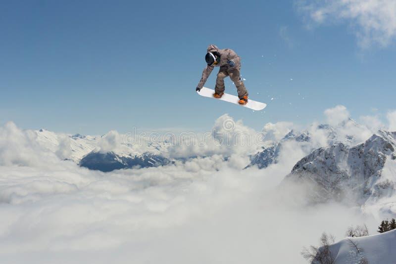 O Snowboarder salta nas montanhas, esporte do extremo do inverno imagem de stock