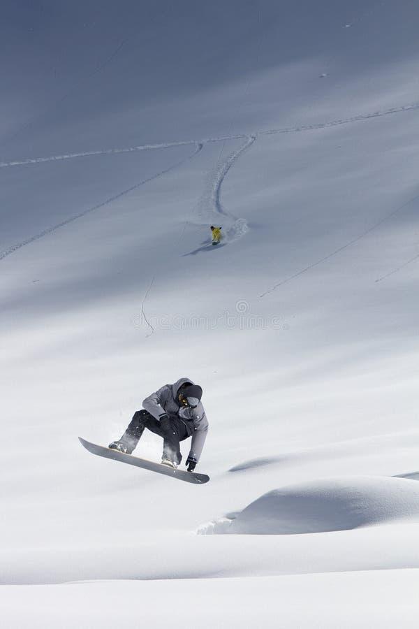 O Snowboarder salta nas montanhas, esporte do extremo do inverno imagens de stock