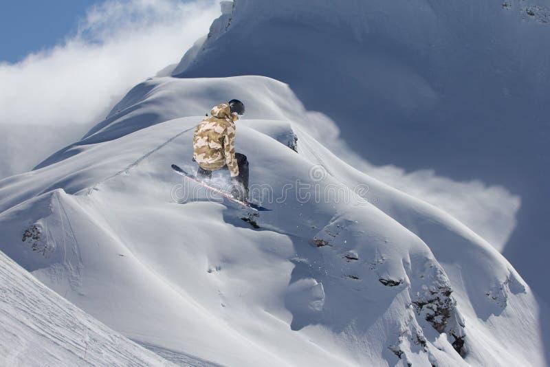 O Snowboarder salta nas montanhas, esporte do extremo do inverno imagem de stock royalty free