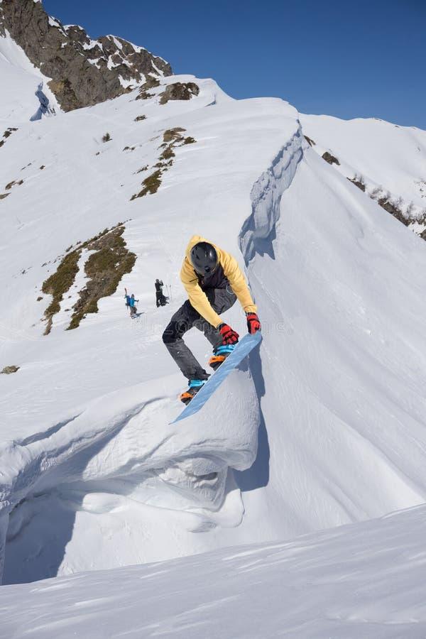 O Snowboarder salta nas montanhas, esporte do extremo do inverno imagens de stock royalty free