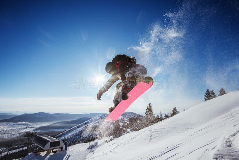 O Snowboarder salta no contexto do céu azul no truque das montanhas imagem de stock