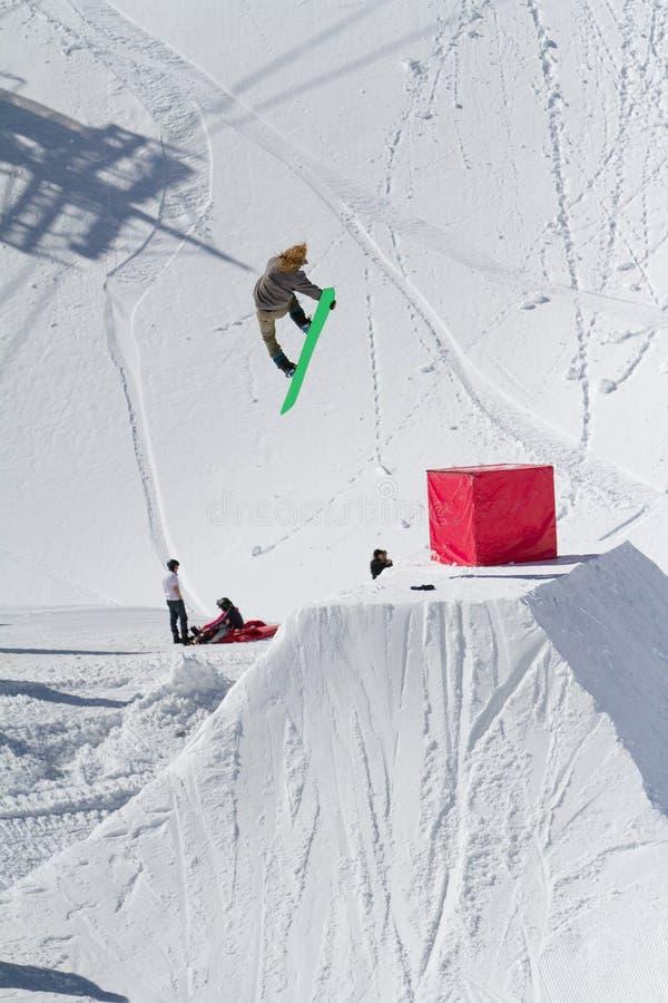 O Snowboarder salta no parque da neve, estância de esqui imagens de stock
