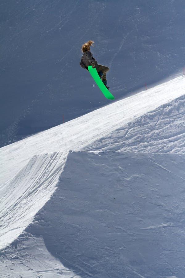 O Snowboarder salta no parque da neve, estância de esqui fotos de stock