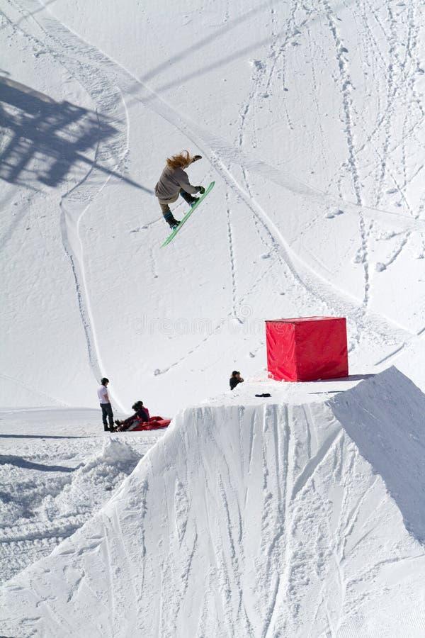 O Snowboarder salta no parque da neve, estância de esqui fotografia de stock royalty free