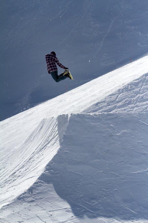O Snowboarder salta no parque da neve, estância de esqui imagens de stock royalty free