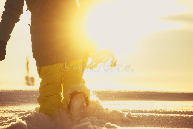 O Snowboarder vai no monte de neve no fundo da luz solar foto de stock royalty free