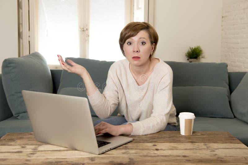 O sofá atrativo e ocupado novo do sofá da mulher em casa que faz algum trabalho do laptop na vista do esforço preocupou-se em lif fotos de stock