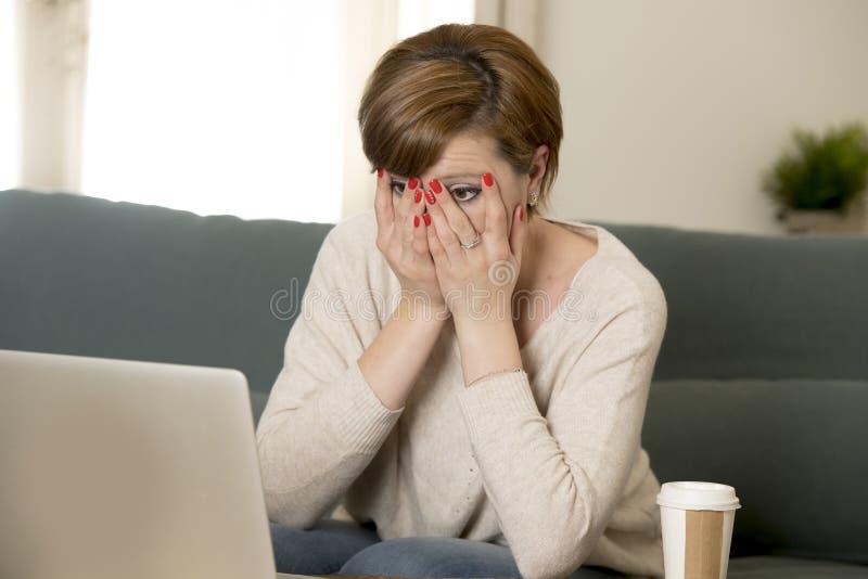 O sofá atrativo e ocupado novo do sofá da mulher em casa que faz algum trabalho do laptop na vista do esforço preocupou-se em lif imagens de stock royalty free