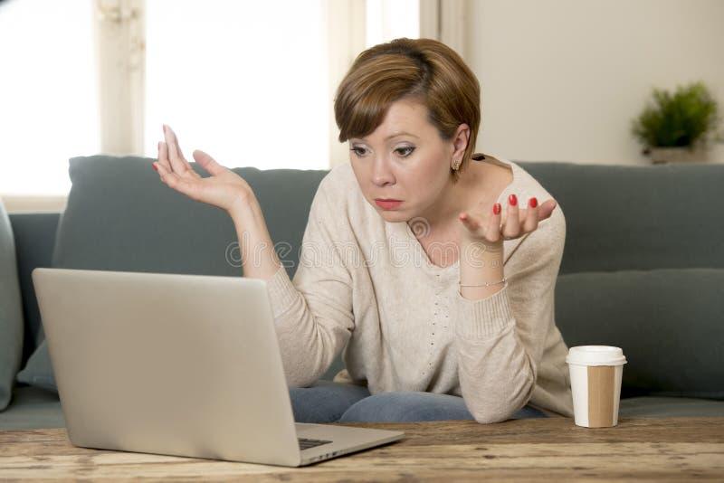 O sofá atrativo e ocupado novo do sofá da mulher em casa que faz algum trabalho do laptop na vista do esforço preocupou-se em lif imagem de stock