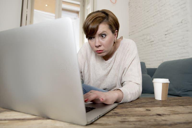 O sofá atrativo e ocupado novo do sofá da mulher em casa que faz algum trabalho do laptop na vista do esforço preocupou-se em lif foto de stock