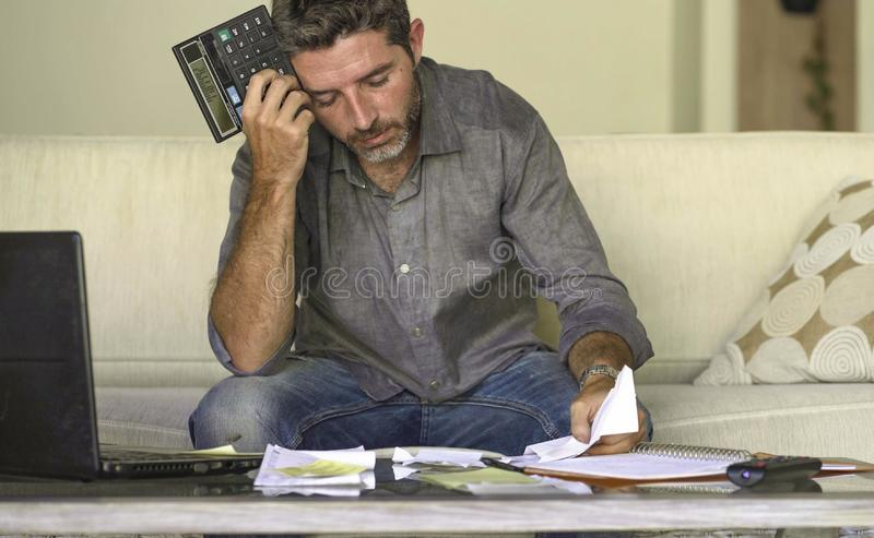 O sofá em casa forçado e desesperado da sala de visitas do homem que faz a contabilidade doméstica com sentimento do documento e  imagens de stock royalty free