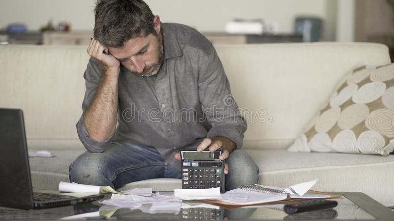 O sofá em casa forçado e desesperado da sala de visitas do homem que faz a contabilidade doméstica com sentimento do documento e  fotografia de stock