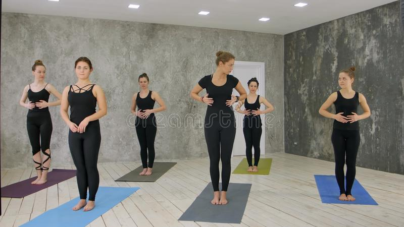 O sofá fêmea novo bonito explica o exercício de respiração da ioga, praticando ao estar fotos de stock