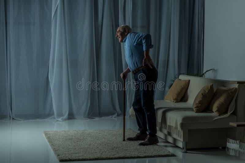 O sofrimento do homem superior da dor nas costas inclina-se em um bastão em vazio imagens de stock