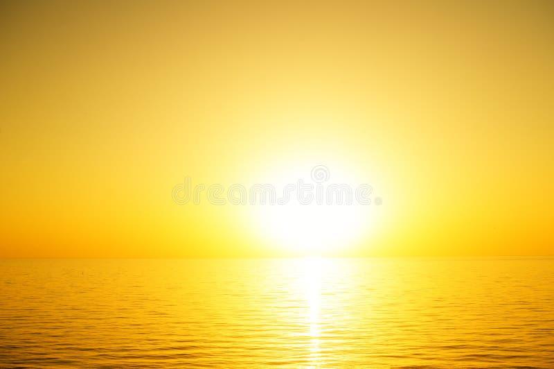 O sol a ajustar-se sobre o horizonte de mar fotografia de stock royalty free