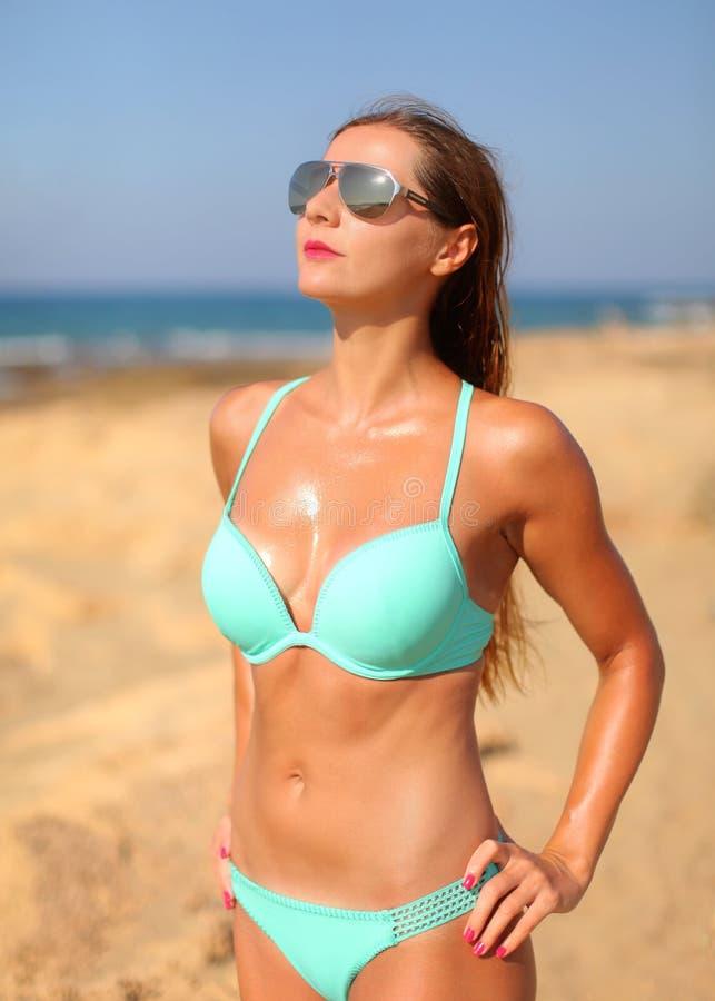 O sol atlético novo da mulher bronzeou-se, os óculos de sol, vestindo o azul ciano b imagem de stock