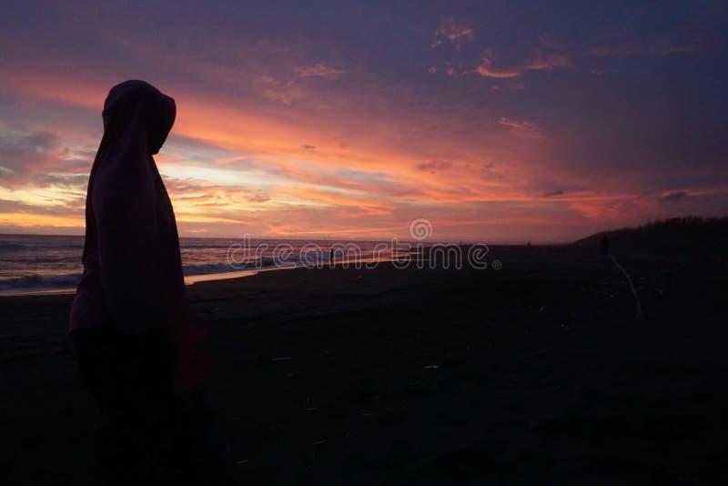 O sol aumenta durante o ver?o na praia com o primeiro plano do silhoutte humano fotografia de stock royalty free
