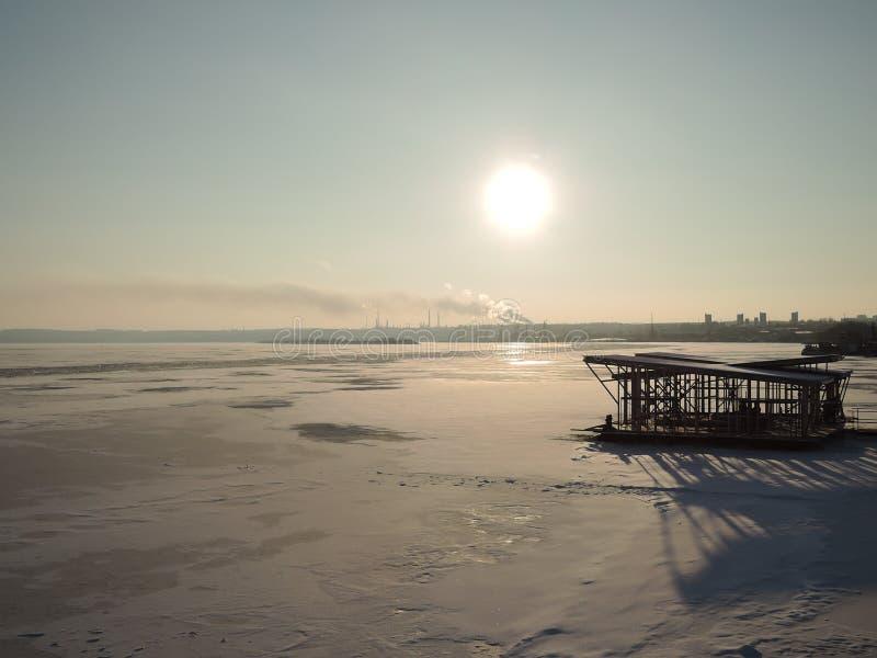 O sol brilhante do inverno brilha sobre o rio congelado coberto com o gelo e ninguém está ao redor fotos de stock