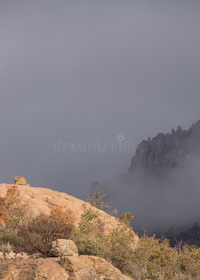 O sol da manhã no monte rochoso com névoa encobriu a montanha no fundo imagem de stock