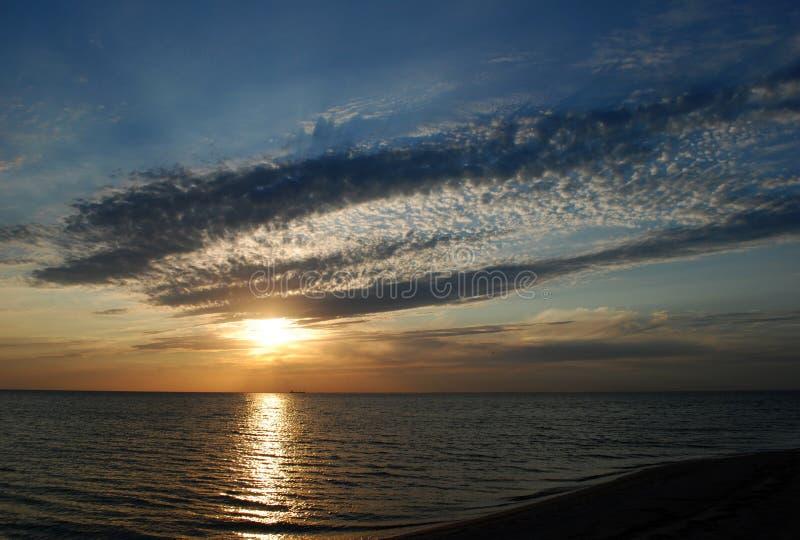 O sol de ajuste nas nuvens acima do mar foto de stock royalty free