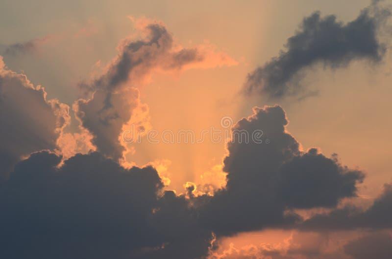 O sol de aumentação é escondido pelas nuvens, enchendo o céu com as cores do nascer do sol fotos de stock royalty free