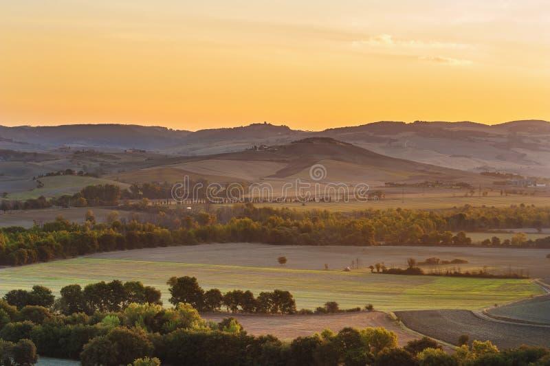 O sol de aumentação sobre os campos de Tuscan fotos de stock royalty free