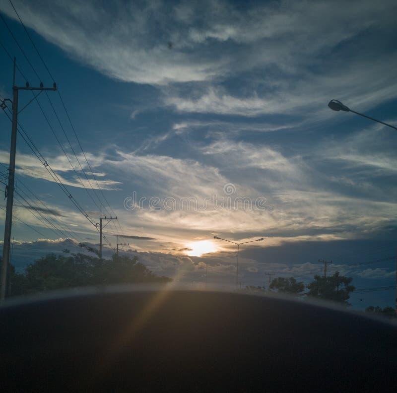 O sol de nivelamento brilha através das nuvens através dos olhos do motorista imagens de stock