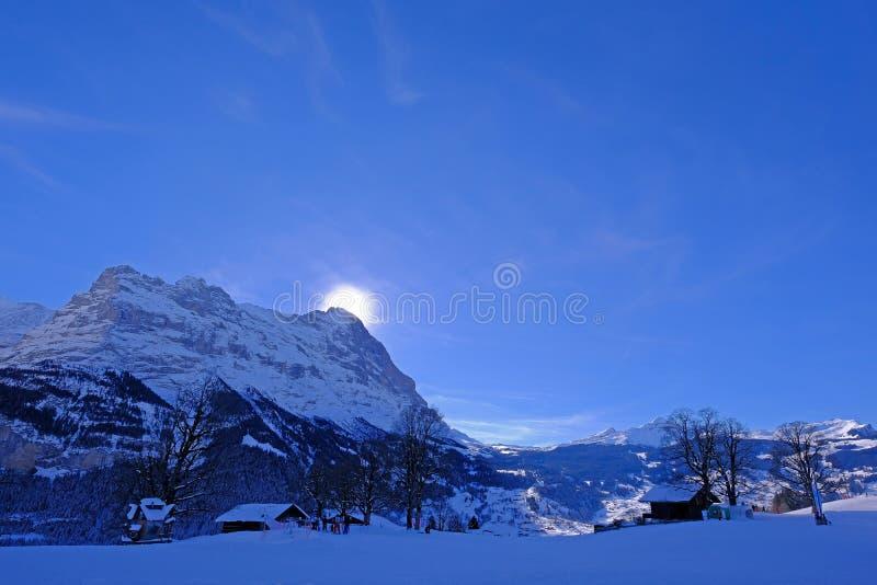 O sol esconde atrás do pico famoso da montanha de Eiger acima de Grindelwald, com muita neve, Berna, Suíça imagem de stock