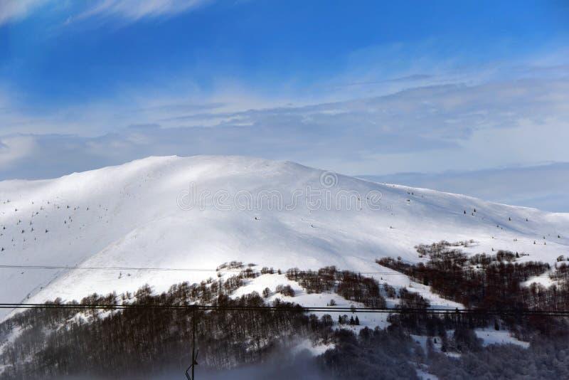O sol está brilhando na montanha nevado foto de stock