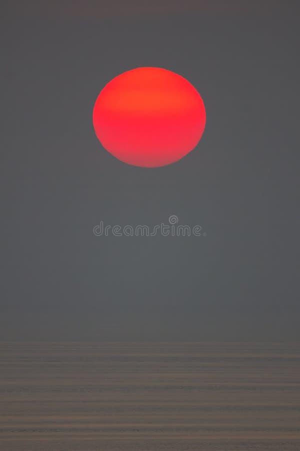O sol está caindo no mar É orangotango da cor o céu e o mar é escuro imagem de stock