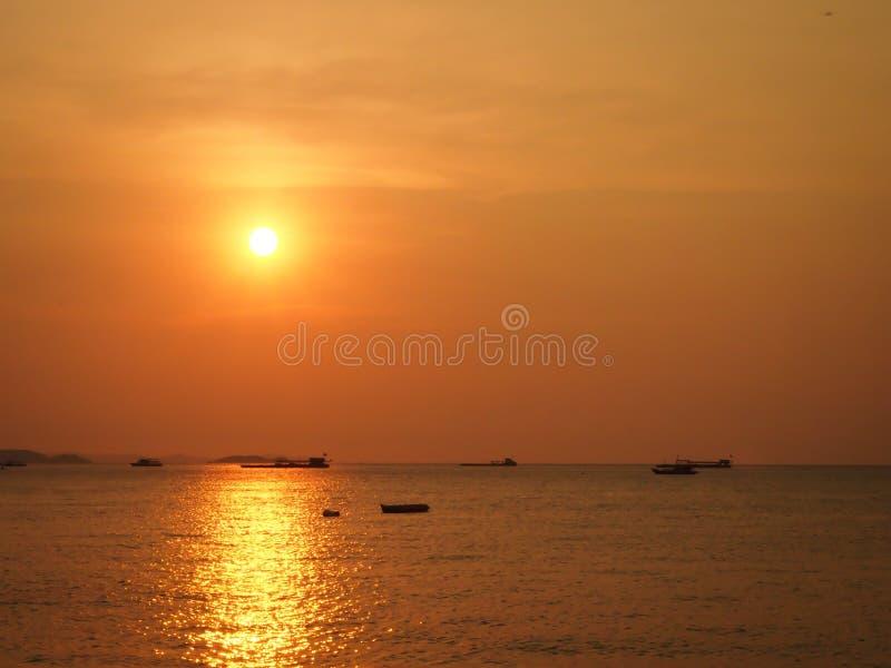 O sol está a ponto de ajustar-se no mar com o surroundi de flutuação dos barcos fotos de stock