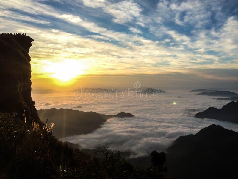 O sol levanta-se acima das nuvens do mar e do ouro imagem de stock