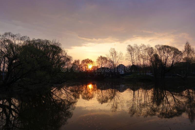 O sol levanta-se acima das nuvens do mar e do ouro alvorecer O sol ? refletido no lago Paisagem rural R?ssia imagem de stock royalty free