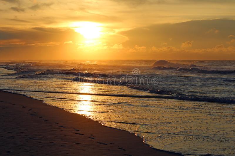 O sol nasce sobre o oceano e a praia o fotografia de stock