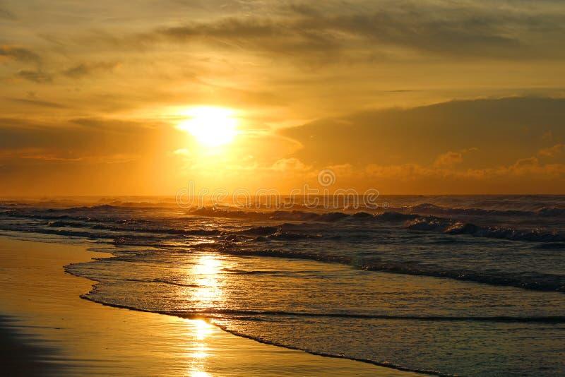 O sol nasce sobre o oceano e a praia o fotografia de stock royalty free