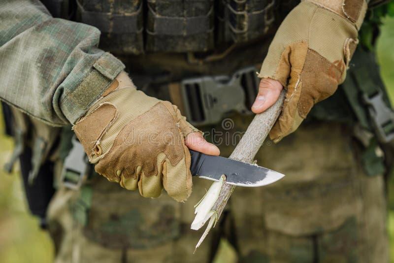O soldado com uma faca cortou uma vara de madeira fotos de stock