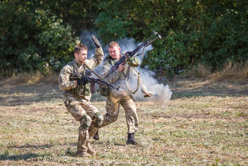 O soldado do destacamento do objetivo especial joga uma granada de fumo no campo fotografia de stock