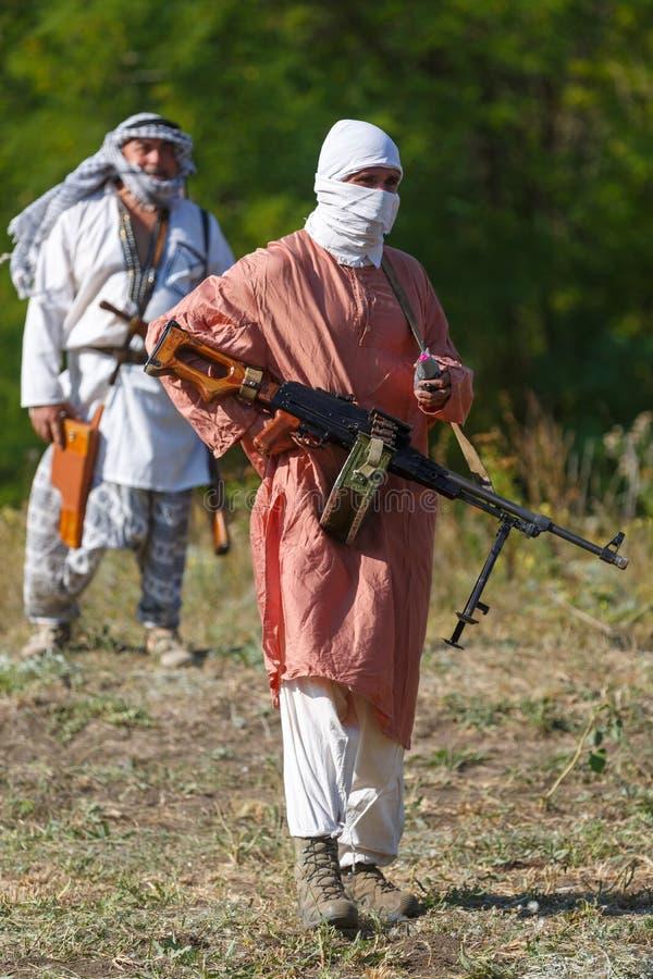 O soldado encoberto está estando com a metralhadora do Kalashnikov em suas mãos imagens de stock royalty free