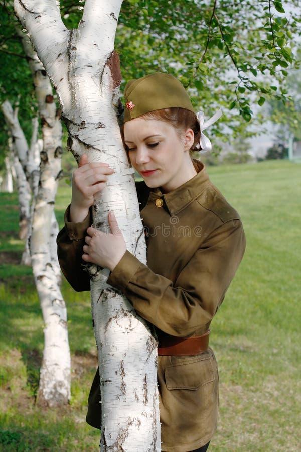 O soldado fêmea soviético no uniforme da segunda guerra mundial está perto do vidoeiro imagem de stock